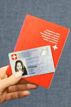 main qui tient une carte d'identité ainsi qu'une passeport suisse